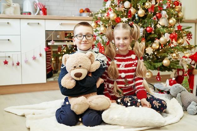 Broer en zus zitten in de buurt van de kerstboom met knuffels