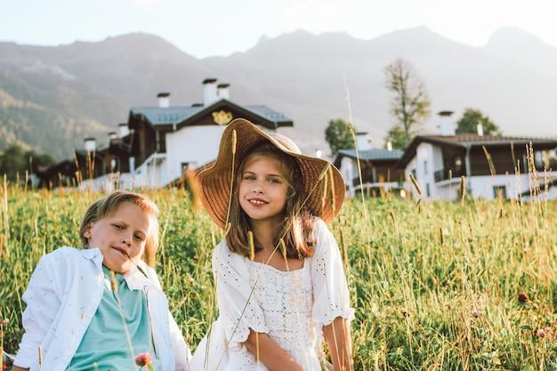 Broer en zus zitten in het gras