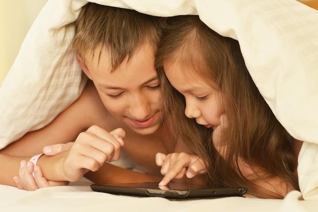 Broer en zusje in bed met tablet pc