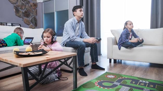 Broer en zussen spelen van videogames in de woonkamer