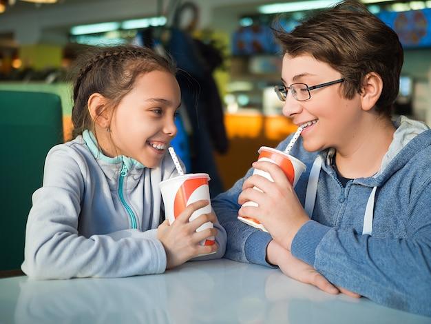 Broer en zuster die consumptiemelk drinken in een café