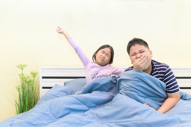 Broer geeuwt en zuster rekt zich in bed uit