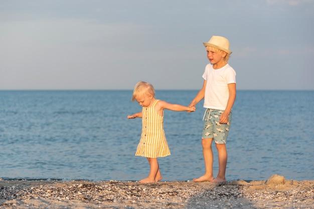 Broer houdt zijn kleine zusje bij de hand en loopt op blote voeten langs het strand