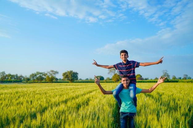 Broer meeliften zijn kleine broertje in tarweveld, landelijk india