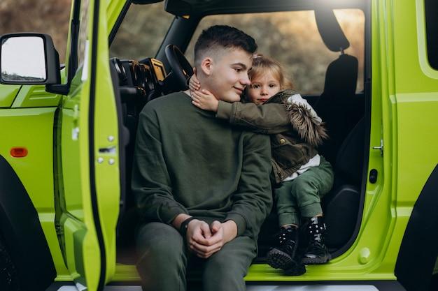 Broer met kleine zusje zit in de groene auto