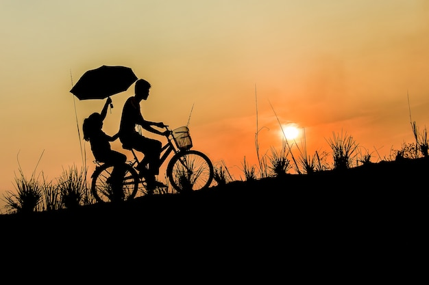 Broer met zus fietsen bij zonsondergang