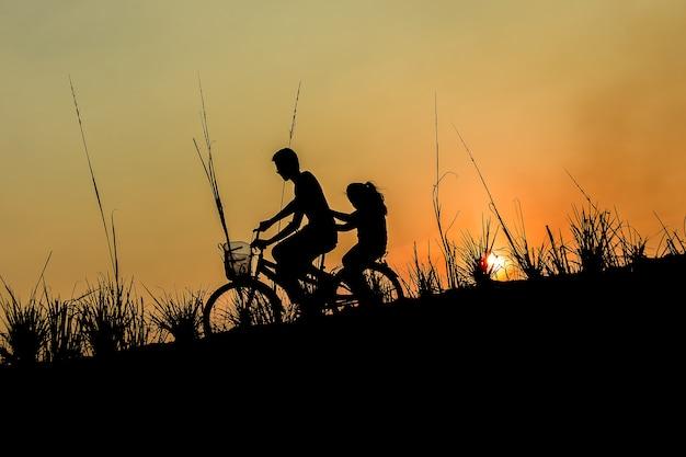 Broer met zus fietsen rijden bij zonsondergang