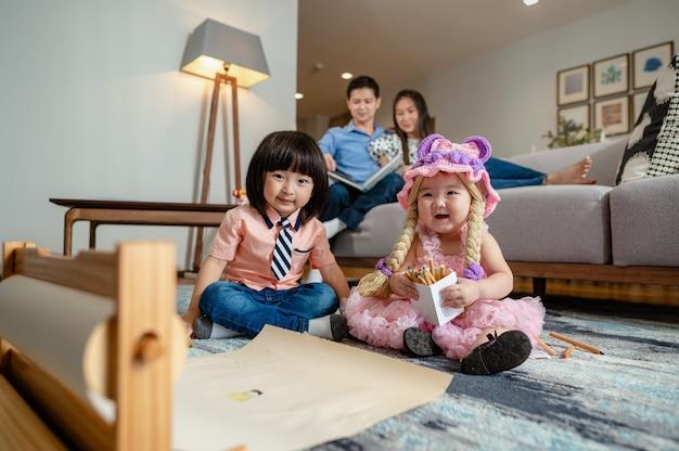 Broer was aan het spelen met zijn zus hij stak zijn hand op en lachte om het kleine zusje op het tapijt