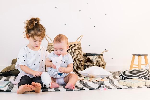 Broer / zus spelen met speelgoed op gestreepte doek