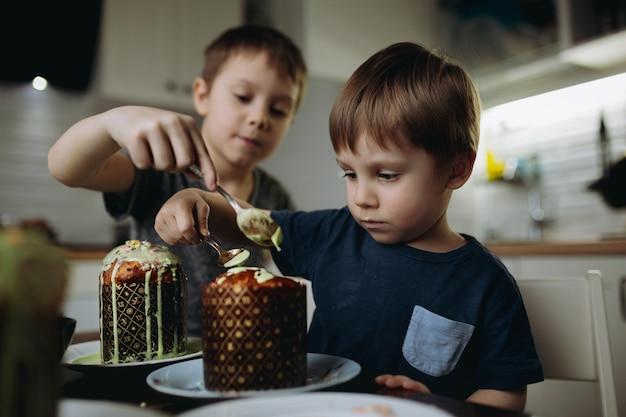 Broers die paascakes versieren met glace icing en sugar topping. afbeelding met selectieve aandacht. hoge kwaliteit foto