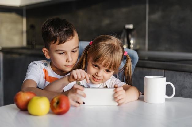 Broers en zussen aan tafel spelen op mobiele telefoon