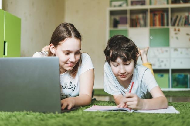 Broers en zussen broer zus aantrekkelijk meisje tiener en tween jongen huiswerk leren vreemde taal schrijven in leerling boek met geopende laptop op de kamer thuis dicteren onderwijs