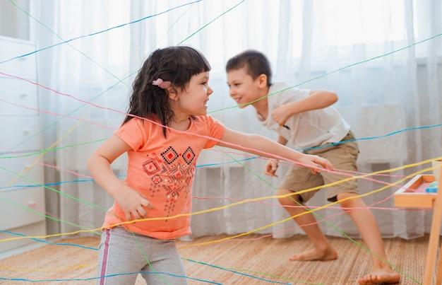 Broers en zussen die door een touwweb gaan