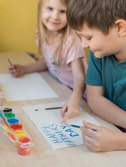 Broers en zussen die een cadeau voor hun vader tekenen