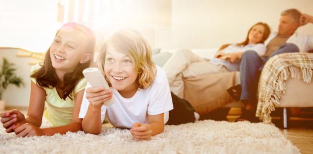 Broers en zussen die op de grond liggen tv te kijken