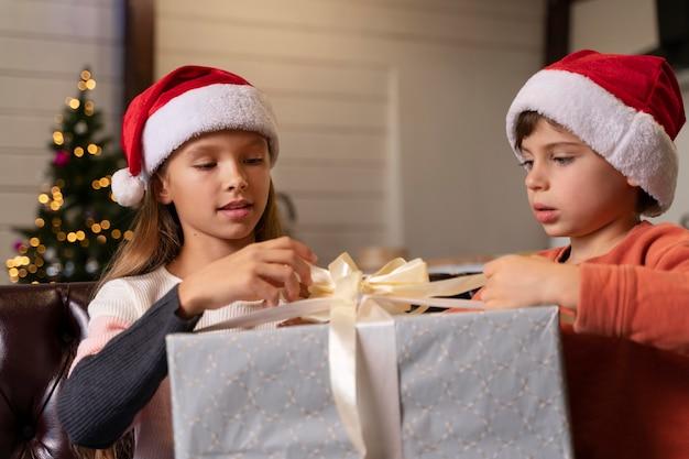 Broers en zussen die samen een kerstcadeau openen