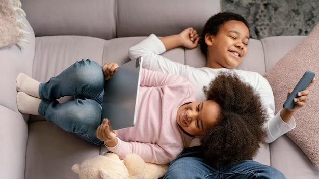 Broers en zussen die thuis tablet en mobiel gebruiken