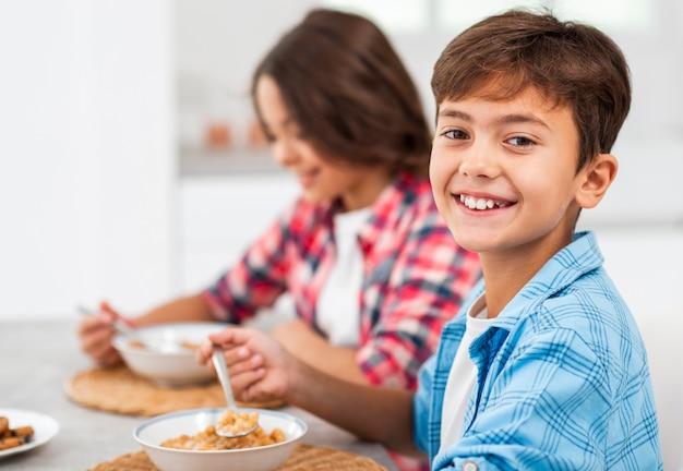 Broers en zussen die van zijaanzichtsmiley ontbijt eten