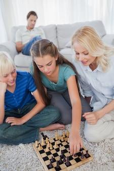 Broers en zussen en moeder schaken zittend op een tapijt