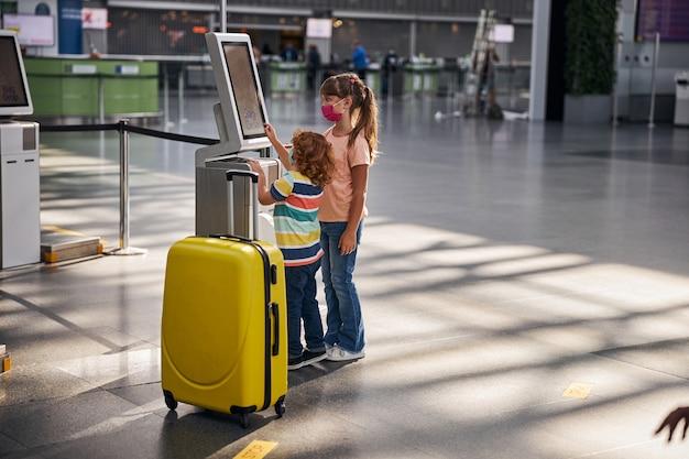 Broers en zussen gebruiken zelfbedieningsautomaat voor bagage