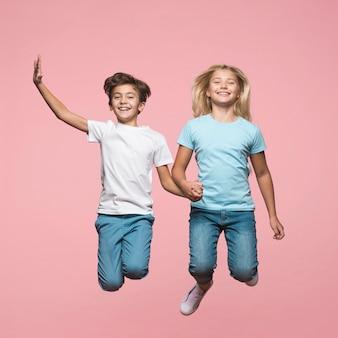 Broers en zussen hand in hand en springen