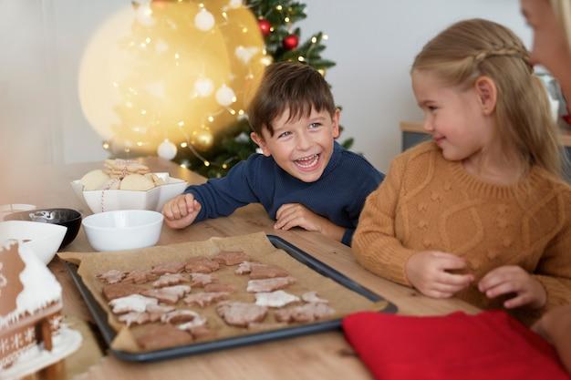 Broers en zussen hebben plezier na het bakken van peperkoekkoekjes