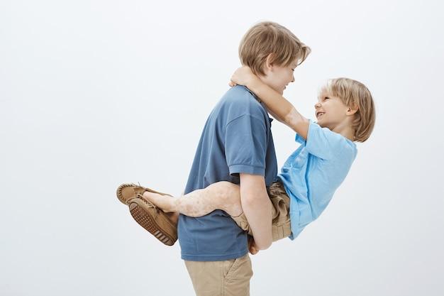 Broers en zussen helpen elkaar altijd. portret van onbezorgde gelukkige jongen die broer in wapens houdt en naar hem glimlacht terwijl hij in profiel staat
