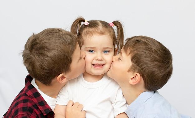 Broers en zussen houden van zorg en genegenheid. oudere broer zoenen zusje op wang en gelukkige familie