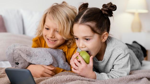 Broers en zussen in bed kijken naar video op de telefoon