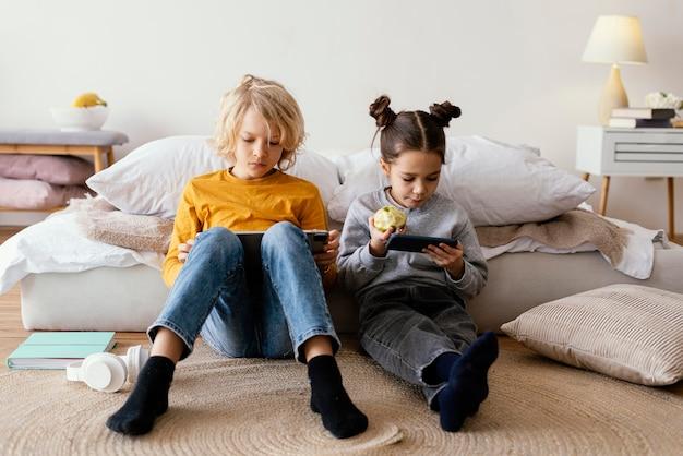 Broers en zussen in bed spelen op mobiel en tablet
