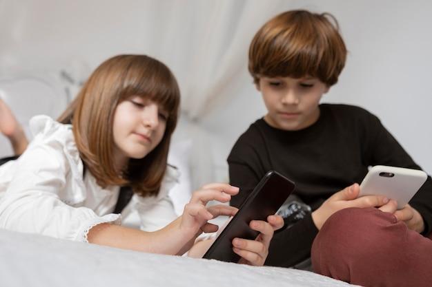 Broers en zussen in de slaapkamer met telefoon