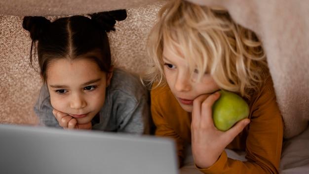 Broers en zussen kijken naar video op laptop
