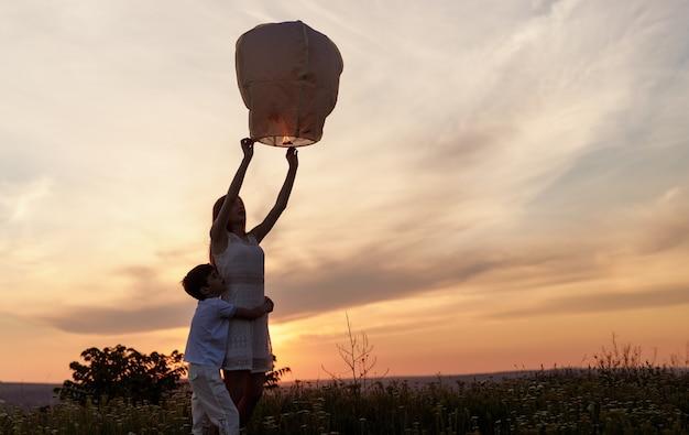 Broers en zussen knuffelen en lanceren papieren lantaarn