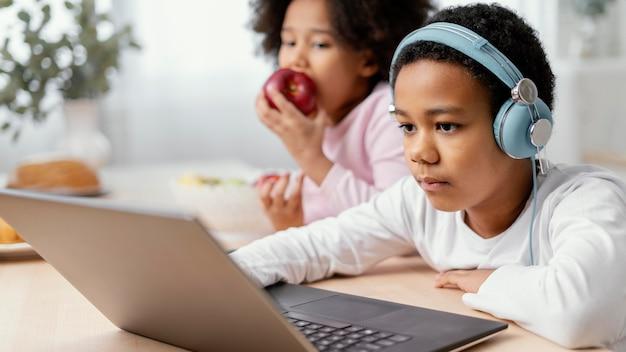 Broers en zussen luisteren naar muziek en gebruiken laptop