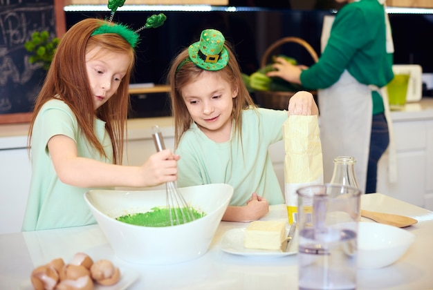 Broers en zussen mengen groene fondantsuikerglazuur