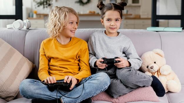 Broers en zussen op de bank met joysticks spelen