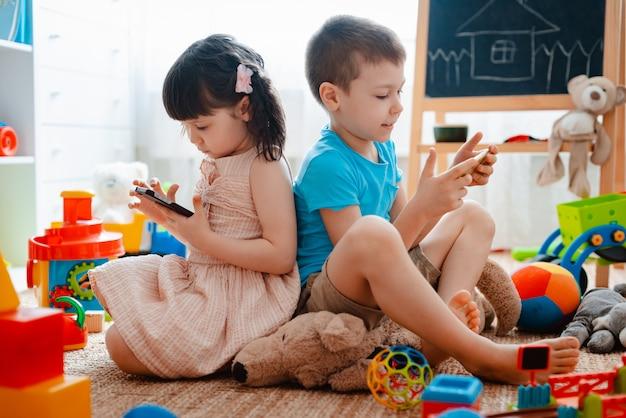 Broers en zussen op de vloer spelen met smartphones
