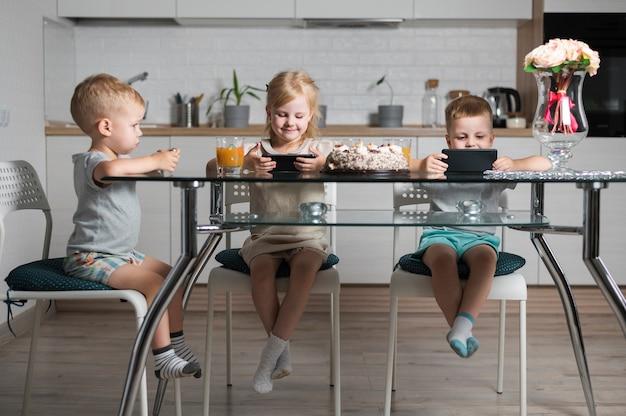 Broers en zussen spelen met hun smartphones