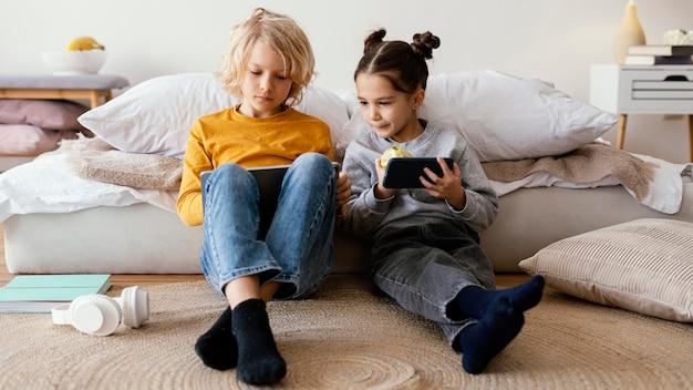 Broers en zussen spelen met mobiel en tablet