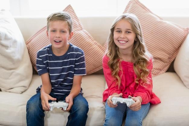 Broers en zussen spelen van videogames in de woonkamer