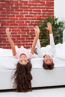 Broers en zussen thuis in bed gelegd en hand in hand