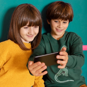 Broers en zussen thuis met behulp van mobiel