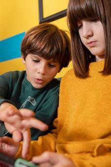 Broers en zussen thuis met behulp van tablet
