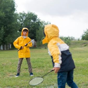 Broers in regenjas badminton spelen