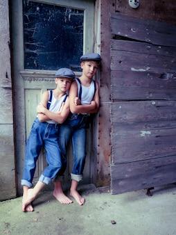 Broers met bretels en hoeden die in het zonlicht op een oud houten gebouw leunen