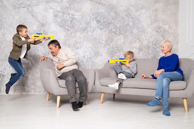 Broers spelen met wapens en rennen rond opa en oma in de woonkamer. een jongen springt en schiet van achter grootvader op zijn broer