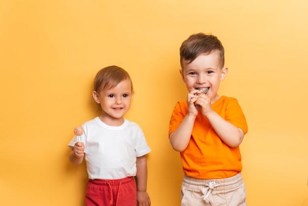 Broertje en zusje eten een zoete lolly op een stokje. gele achtergrond. het concept van preventie van cariës en diabetes bij kinderen.