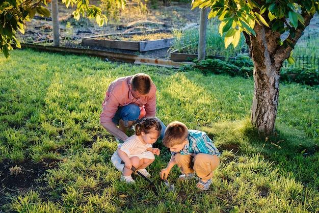 Broertje en zusje planten zaden met hun vader