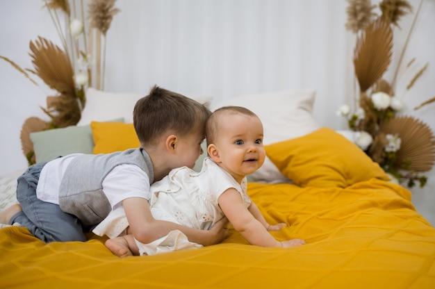 Broertje en zusje spelen op een gele wollen deken op het bed in de kamer