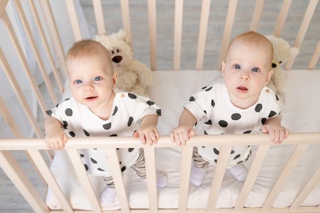 Broertje en zusje van een tweelingbroer zitten in hun pyjama in de wieg